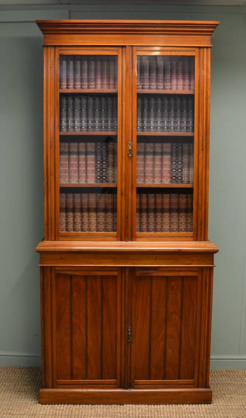 Victorian Walnut Large Antique Bookcase/Glazed Dresser This distinctive Victorian walnut large antique bookcase/glazed dresser, circa 1890, has a moulded cornice above two glazed doors with original handle fronting the interior which benefits from three adjustable shelves. The lower section of the antique bookcase has a rectangular moulded top above two cupboard doors with key and working lock and distinctive reeded panels.