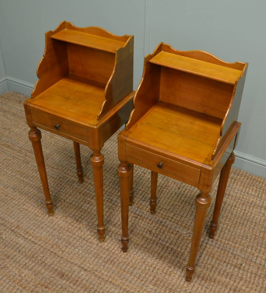 Pair of Edwardian Birch Antique Bedside Tables. This rare pair of Edwardian antique bedside tables date from around 1910 and are made from birch. They have unusual shaped backs with a small shelf above moulded tops and a frieze drawer with brass knobs. The antique tables stand on four beautifully turned legs and are a golden shade of birch.