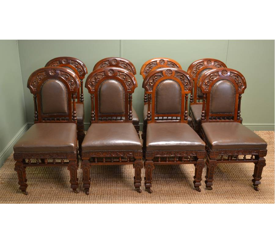 Superb Set of Eight Victorian Antique Walnut Dining Chairs This rare set of eight walnut antique dining chairs are of superb quality and by the renowned cabinet makers A Blain Liverpool . They have even been seen on location in Coronation Street! The chairs have unusual curved backs with quality floral and leaf carvings along with turned upright supports and lower turned gallery. They stand on splayed back legs with quality carved front legs along with decorative apron. The chairs are upholstered, both on the back and seat, in a brown leather which is in good condition and finished with a stud trim. One chair does have an old repair, which does not distract from its striking looks, but is still very sturdy and good for everyday use.